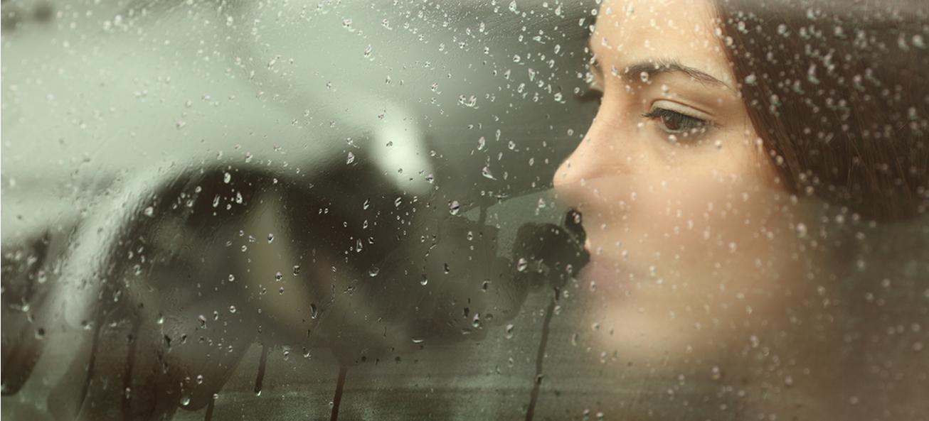 Frau sitzt in depressiver Haltung auf einer Parkbank im Winter